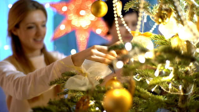 Mature mother and her adult daughter decorate the Christmas tree indoors video