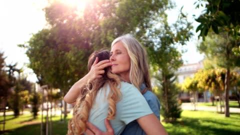 olgun anne ve genç kızı parkta sarılma - kızlar stok videoları ve detay görüntü çekimi