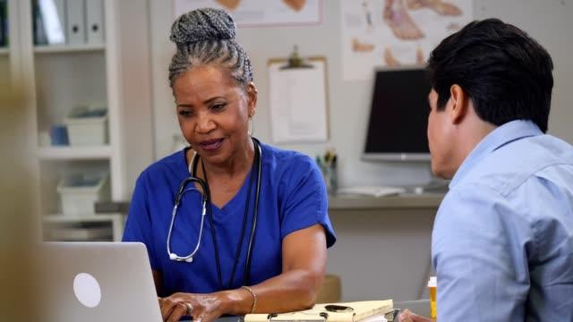 olgun hemşire görüşmeler ve bilgisayarda çalışırken hasta ile gülümsüyor - cerrahi önlük stok videoları ve detay görüntü çekimi