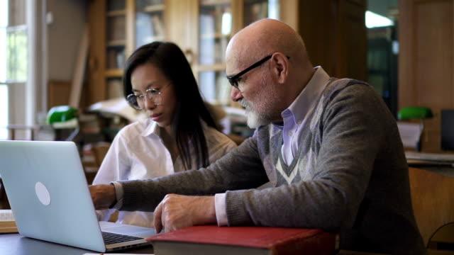 成熟した教授と一緒に働く若い女性アジア学生 - 勉強する点の映像素材/bロール