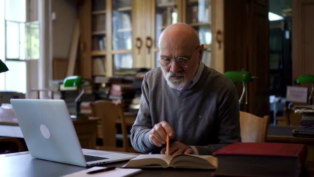 Professeur mature travaillant avec le livre et l'ordinateur portable, assis à table dans la bibliothèque - Vidéo