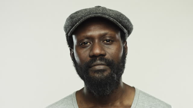 Mature real african man with flat cap staring at camera video