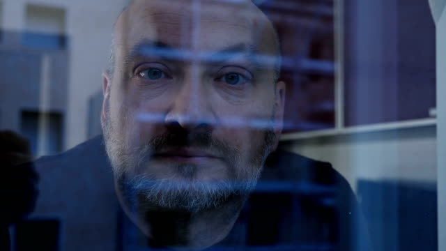 mature serious man staring at the camera from behind the glass - curiosità video stock e b–roll