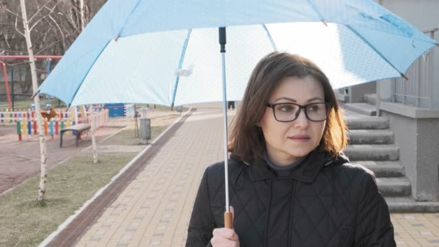 Mature smiled walking woman in coat with glasses with an umbrella, outdoor spring autumn winter season.