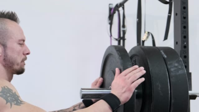 Mature strong man putting weights on the rack at a gym