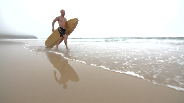 A mature Surfer heads out into the Ocean. video