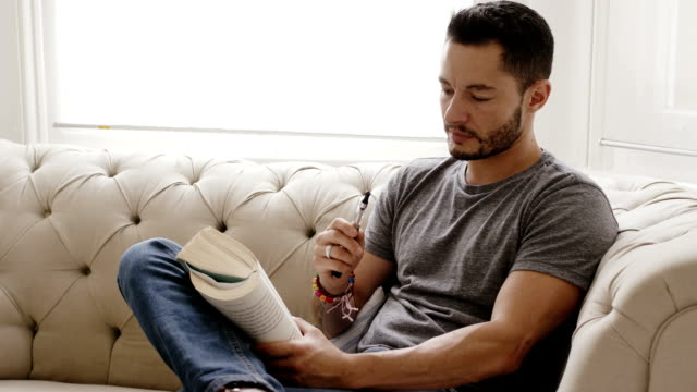 Mature Transgender man reading a book at home Mature man sitting on sofa at home reading a book and smoking electric cigarette transgender stock videos & royalty-free footage