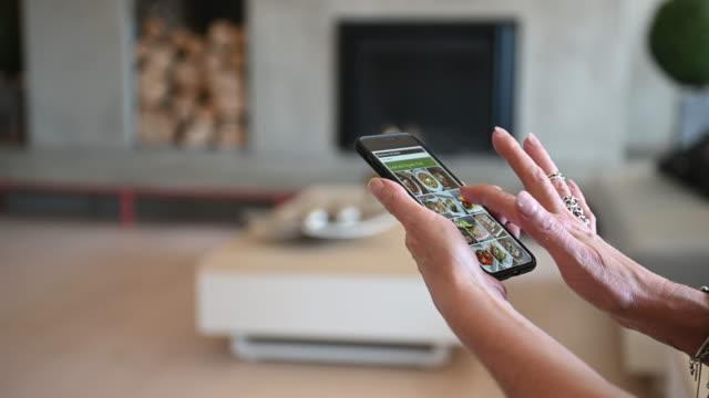 reife frau allein bestellen essen mahlzeit auf mobilen gerät app wohnzimmer - bucht stock-videos und b-roll-filmmaterial