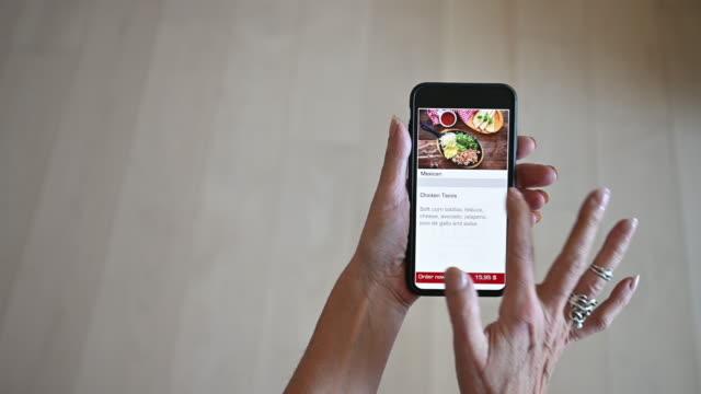 reife frau allein bestellen lebensmittel mahlzeit auf mobilen gerät app - bucht stock-videos und b-roll-filmmaterial