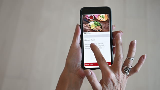 Mature woman alone Ordering Food Meal on mobile device app