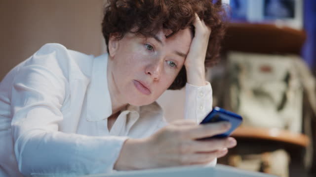 mature woman, an office employee, is using phone - eastern european descent stock videos & royalty-free footage