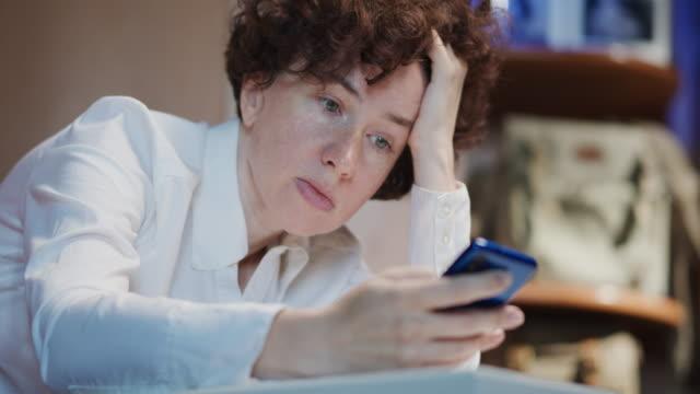 vidéos et rushes de femme mûre, un employé de bureau, utilise le téléphone - une seule femme d'âge mûr