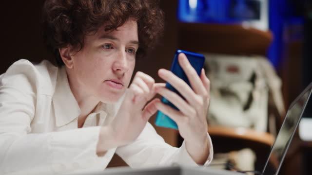 mature woman, an office employee, is using phone - русского происхождения стоковые видео и кадры b-roll
