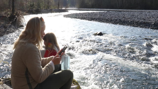 Mature woman and daughter relax on riverbank at sunrise