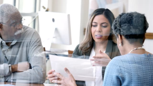 reife frau und ihr mann treffen sich mit weiblicher finanzberaterin - sparsamer lebensstil stock-videos und b-roll-filmmaterial