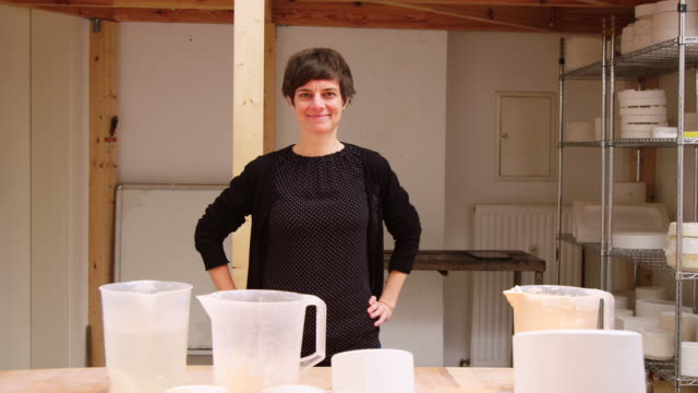Mature woman at pottery studio with hands on hips
