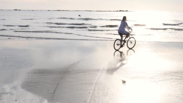 vídeos de stock e filmes b-roll de mature woman bicycles along tidal flat at sunrise - 55 59 anos