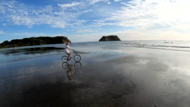 Mature woman bicycles along tidal flat at sunrise