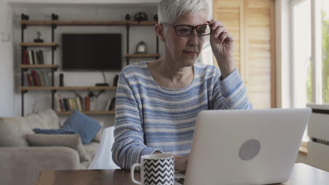 Mature woman blogging on her laptop at home and looking at the camera. video