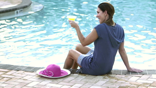 Mature woman by swimming pool with a drink A mature woman relaxing on a pool deck, holding a cocktail. margarita stock videos & royalty-free footage