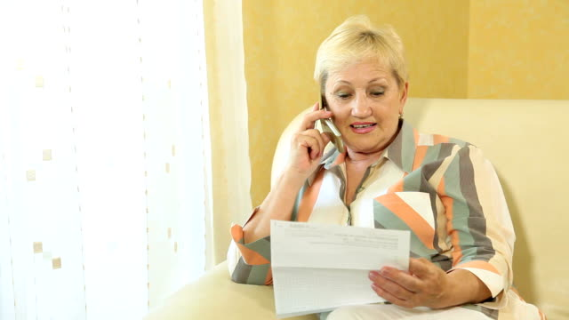Mature woman calling by the phone at home video