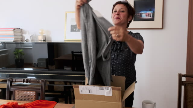 Mature woman checking out clothes purchased online