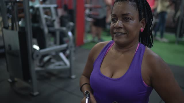 Mature woman doing exercises in the gym