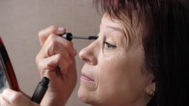 Mature woman doing makeup at home Mature woman paints eyelashes with the brush mascara stock videos & royalty-free footage