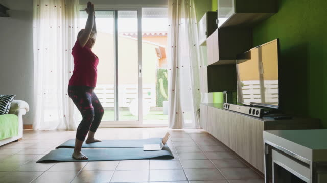 Mature woman doing yoga during the lockdown Handheld video of mature woman doing yoga during the lockdown at home, she is doing the exercises in the living room with her laptop. 50 54 years stock videos & royalty-free footage