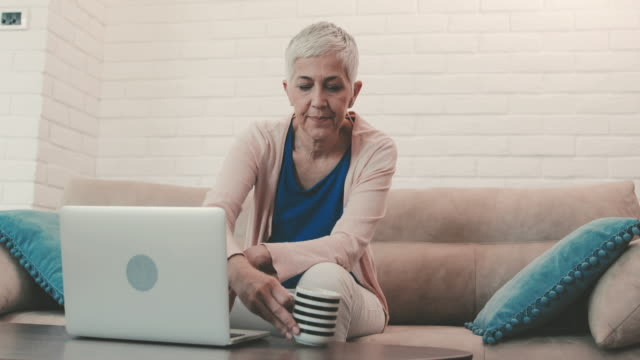 Mature woman drinking coffee after writing an e-mail on laptop at home. video