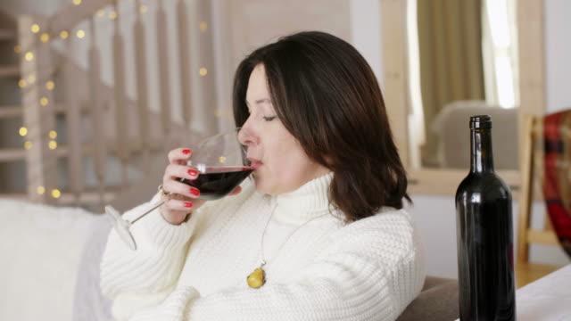 孤独でワインを飲む熟女 - ソファ 女性点の映像素材/bロール