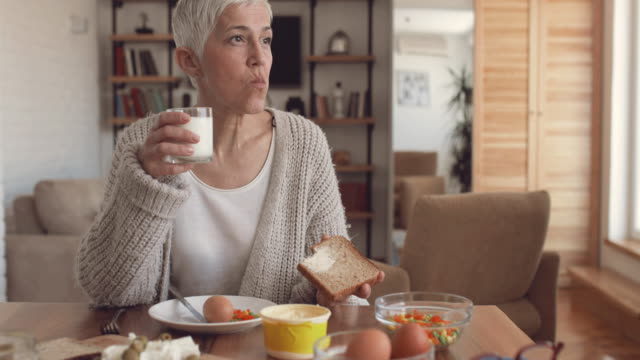 Mature woman eating a breakfast at dining table at home.