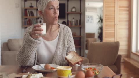 donna matura che mangia una colazione a tavola a casa. - alimentazione sana video stock e b–roll