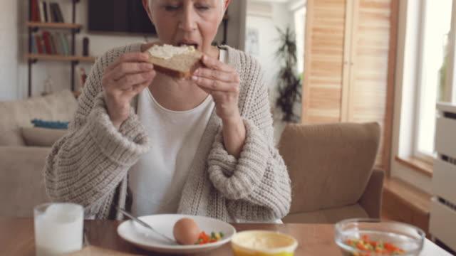 vídeos de stock, filmes e b-roll de mulher madura desfrutando no pequeno-almoço em casa e apresentando okey sinal enquanto olha para a câmera. - gordura