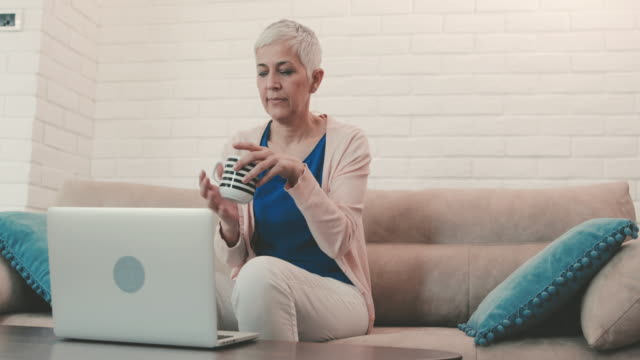 Mature woman enjoying in cup of coffee while sitting on the sofa and using laptop. video