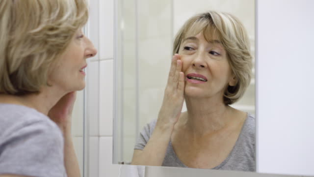 mature woman examining her face in the mirror - woman mirror video stock e b–roll