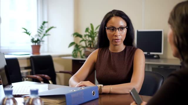 donna matura che spiega le sue preferenze all'agente afro-americano in una società immobiliare - sistema legale video stock e b–roll