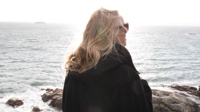 Mature woman explores windy headland In winter; distant coastline visible coastal feature stock videos & royalty-free footage