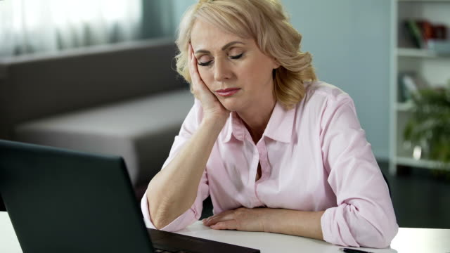 Mature woman falling asleep at workplace, lack of vitamins and energy, tired video