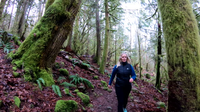 Mature woman follows forest trail