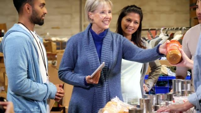 mogen kvinna händer matvaror till volontär på food bank - välgörenhet bildbanksvideor och videomaterial från bakom kulisserna