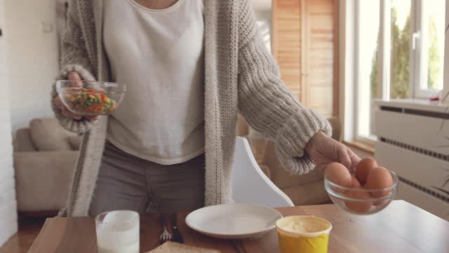 mogen kvinna att ha frukost och njuter av en morgonen hemma. - kokat ägg bildbanksvideor och videomaterial från bakom kulisserna