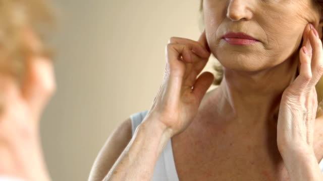 зрелая женщина тяжело вздыхает, глядя на ее морщинистой и провисание кожи в зеркале - морщинистый стоковые видео и кадры b-roll