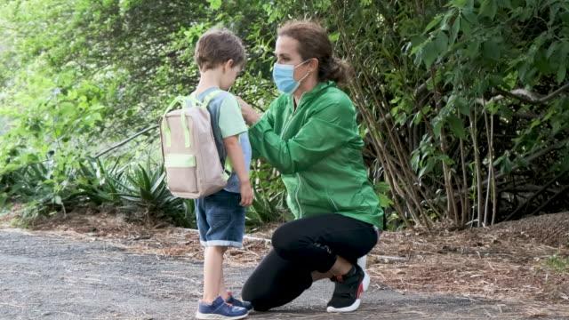 成熟的女人在上學前幫助兒子戴上防護面罩 - back to school 個影片檔及 b 捲影像