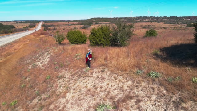 Mature woman hiking in the arid highland in Texas, USA. Aerial drone video with the forward camera motion.