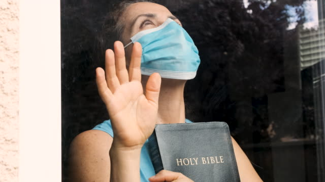 mature woman holding a bible wearing a surgical mask looking through a window - христианство стоковые видео и кадры b-roll