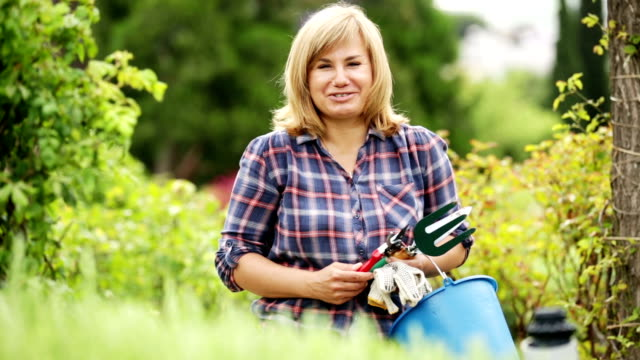 mature woman  holding horticultural tools in garden video
