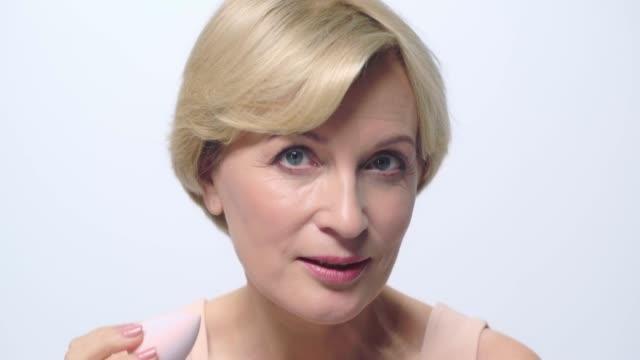vidéos et rushes de femme mûre retenant la bouffée de maquillage près du visage d'isolement sur le blanc - une seule femme d'âge mûr