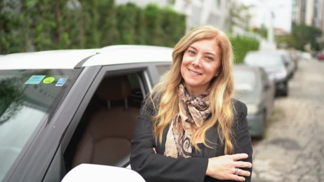 Mature woman in front of a car with arms crossed