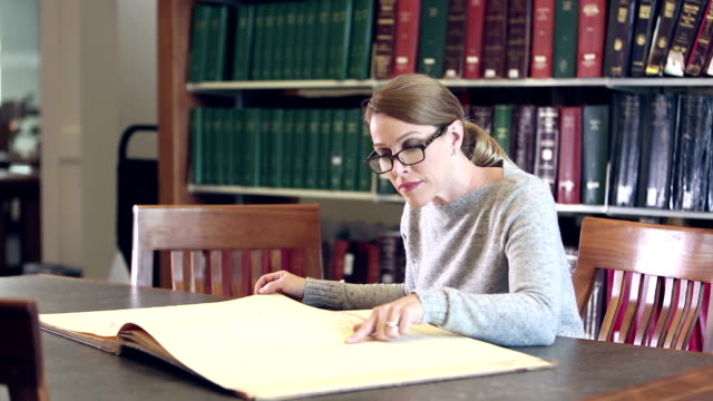 Mature woman in library examining an oversized book